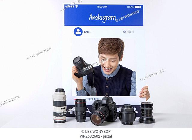 Portrait of young smiling man collecting cameras on SNS