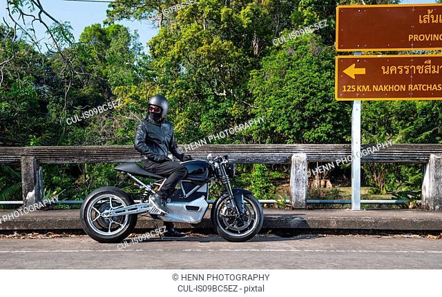 Motorcyclist sitting on motorbike by road sign, Khao Yai national park, Prachin Buri, Thailand