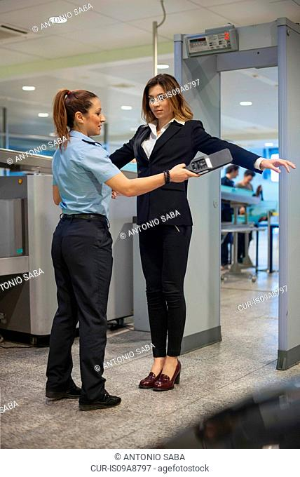 Security guard checking female passenger in airport security