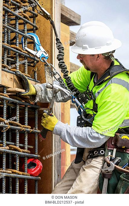Caucasian worker examining wall at construction site
