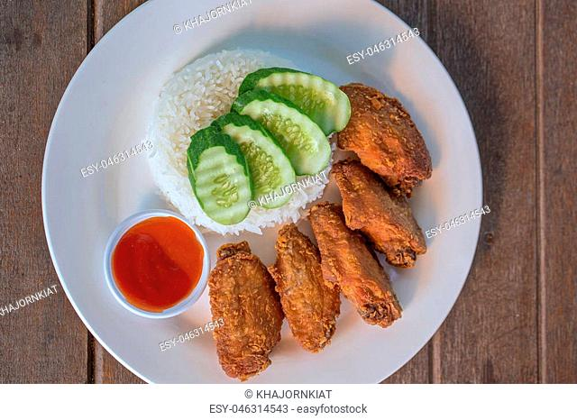 Fried chicken wings lay in a dish placed on a wooden table