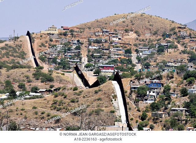 A metal wall, as seen from Arizona, marks the international border between Nogales, Arizona, USA, and Nogales, Sonora, Mexico