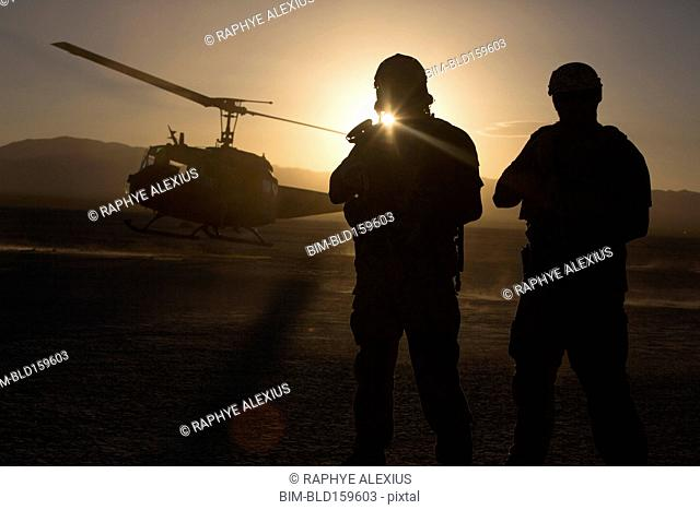 Silhouette of soldiers watching helicopter in desert landscape