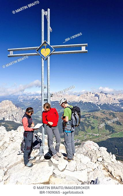 Climbers at the summit cross, Boeseekofel fixed rope route, Dolomites, Fanes group and Heiligkreuzkofel mountain group at the back, province of Bolzano-Bozen