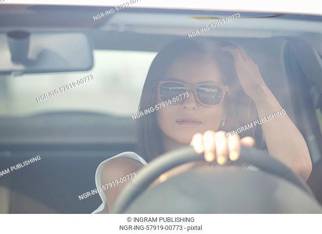Girl wearing sunglasses driving white car