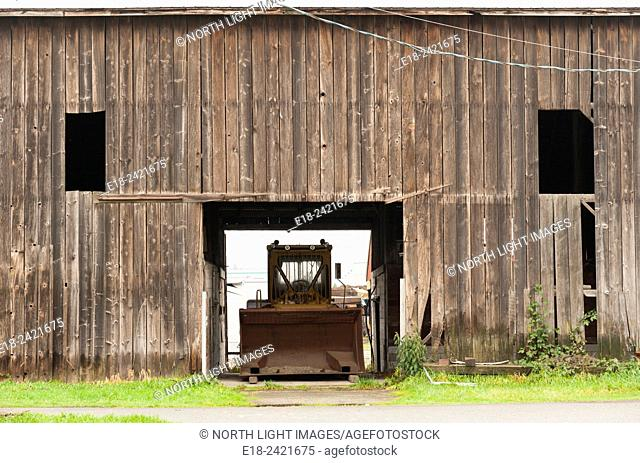 Canada, BC, Delta. Tractor with large shovel parked in barn. Farmland south of Vancouver