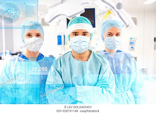 surgery, healthcare, medicine and people concept - group of surgeons in operating room at hospital with diagram and virtual screen projection
