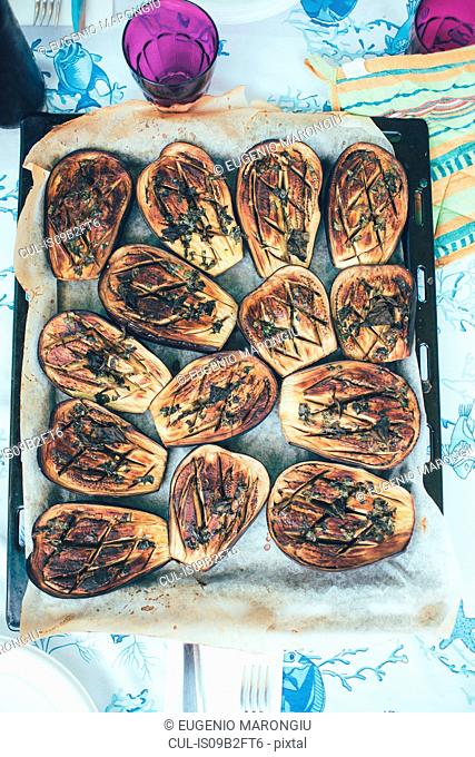 Overhead view of roasted aubergines in baking tray