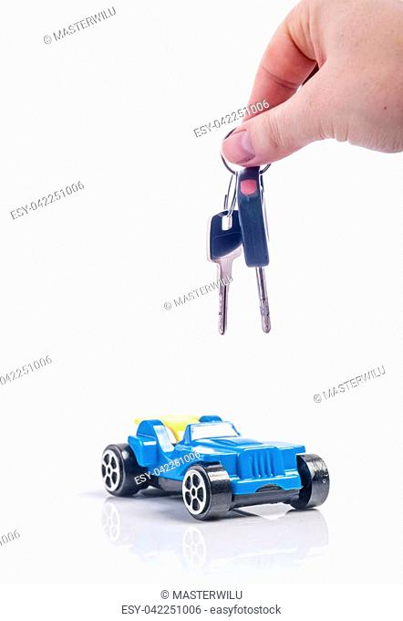 An image of keys above toy blue car