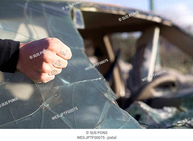 Fist of a young man with HOPE tattoo on broken windscreen on a scrapyard
