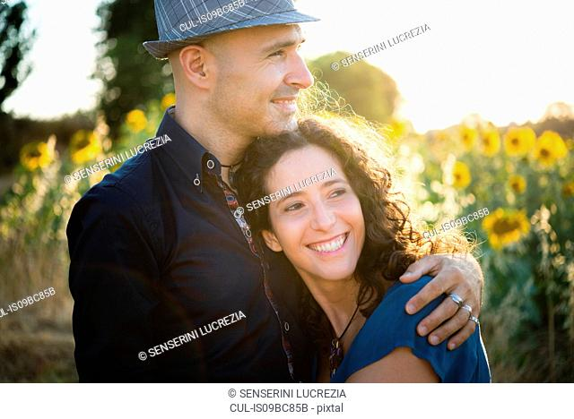 Couple in field of sunflowers, hugging