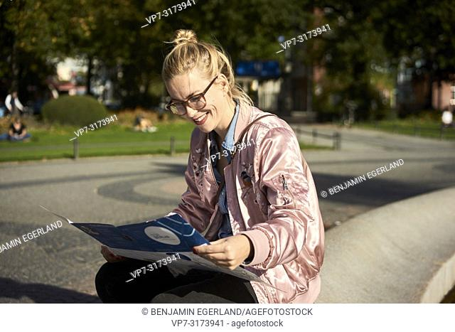 Woman reading city guide map, in Berlin, Germany