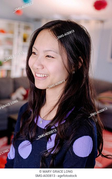 USA, Young woman smiling in living room