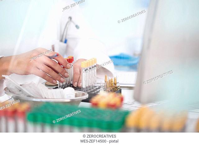 Close-up of lab technician with test tubes and rack in laboratory