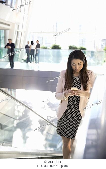 Businesswoman texting with cell phone on escalator in atrium