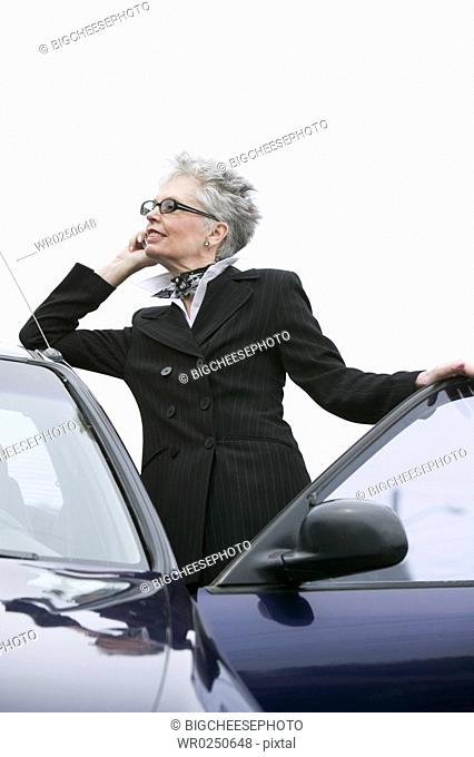 Woman next to car using mobile phone
