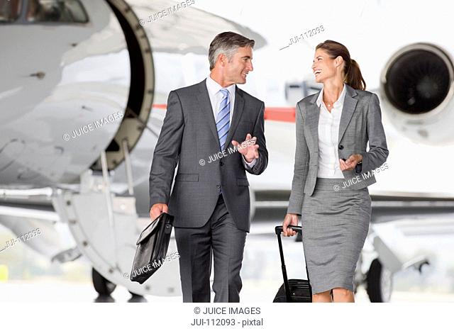 Smiling Businesswoman and Businessman walking away from private jet