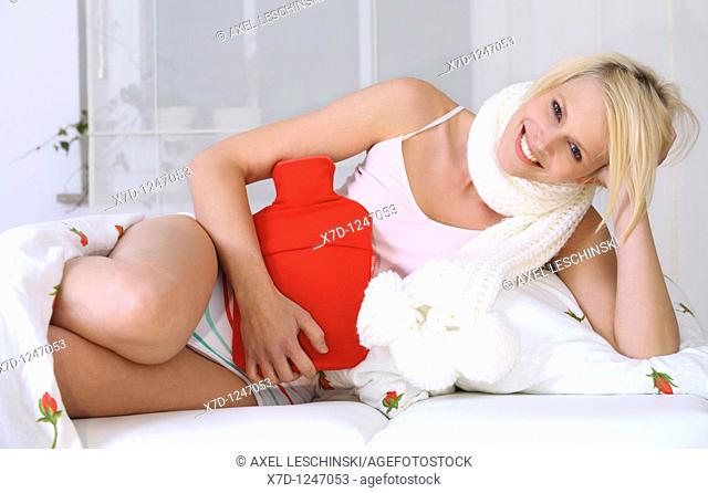 woman in bed holding hot water bottle