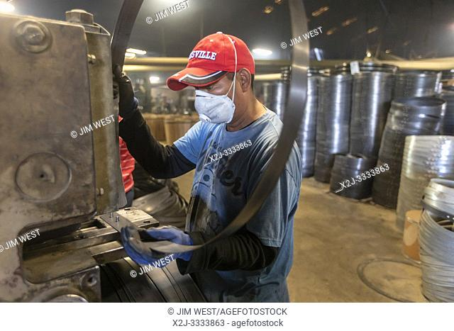 Louisville, Kentucky - Workers at Kelvin Cooperage make oak barrels for aging bourbon and wine. A worker makes metal rings to hold the barrels together