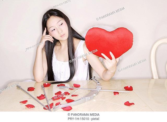 Young woman holding heart shape cushion