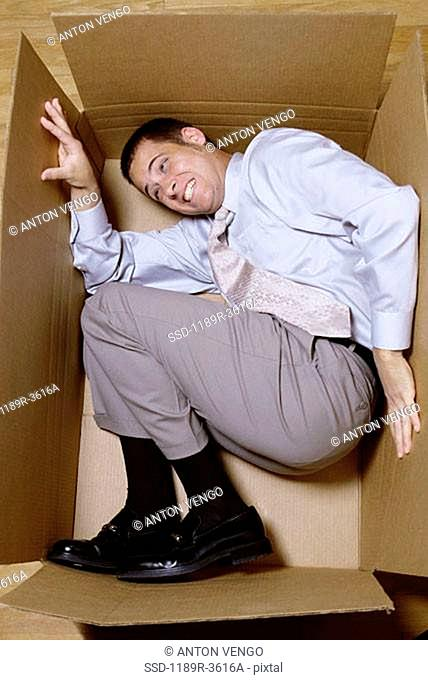 Businessman lying in a cardboard box