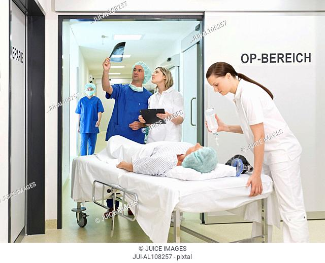 Doctor and nurses taking patient into operating room at hospital and looking at x-rays