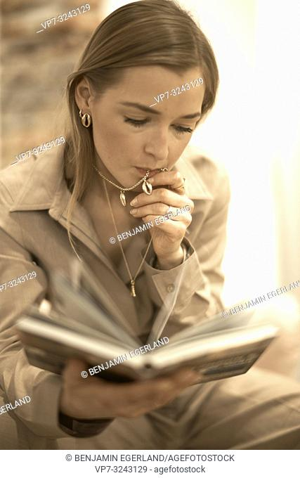 fashionable blogger woman reading book indoors, chewing expensive jewellery necklace chain in mouth, rich, wealthy, in Munich, Germany