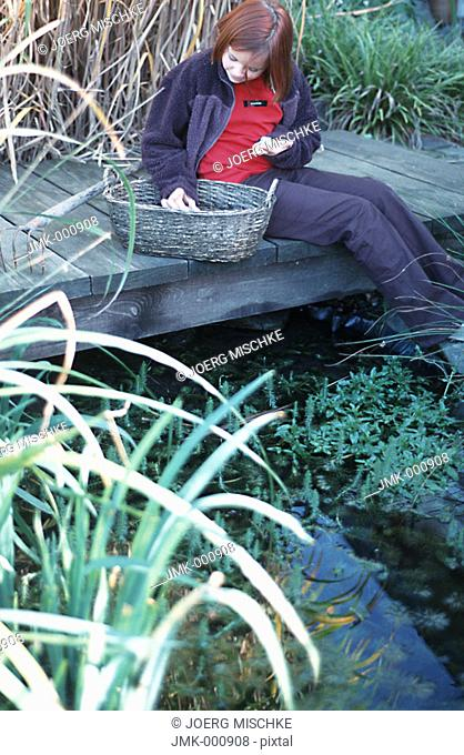 Little girl in the garden, sitting on a footbridge at a pond