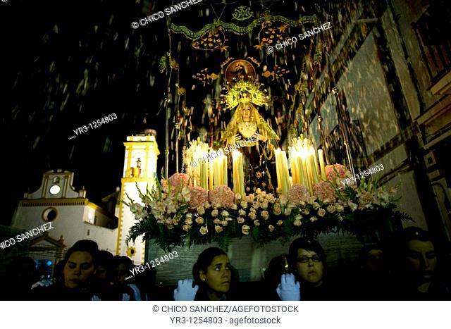 People throw flowers toward a wooden statue of the Virgin of Pain as she is publicly displayed in a Holy Week procession in the town of Prado del Rey in...
