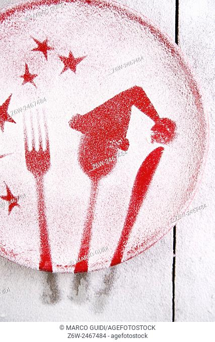 Representation of the Christmas holiday with cutlery on red dish and sprinkle with flour