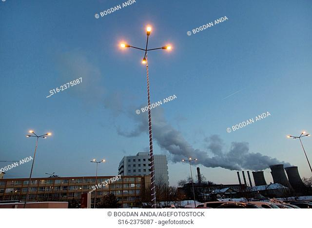 Street lamps on in a parking lot at dusk, with Grozavesti Power Station in the background - Bucharest, Romania, Europe, Eastern Europe