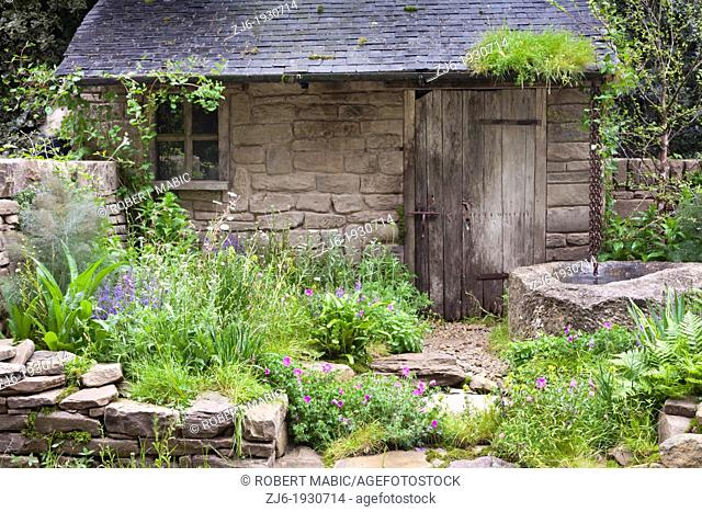 Old cottage garden with well and natural plantings of perennials and grasses. Chelsea Flower Show London England