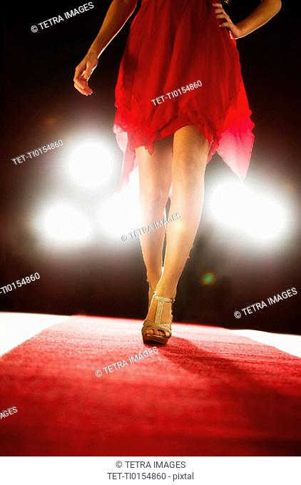 Woman wearing red dress on catwalk