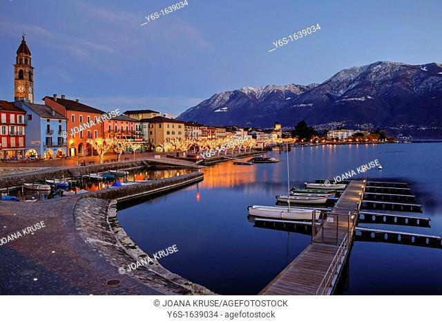 Ascona in Ticino, Switzerland during the Christmas season with illuminated plane at lakefront