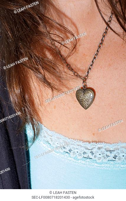Mid section of woman wearing heart shape necklace
