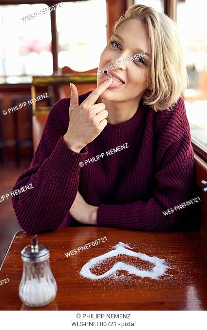 Portrait of smiling blond woman with heart-shaped sugar on table