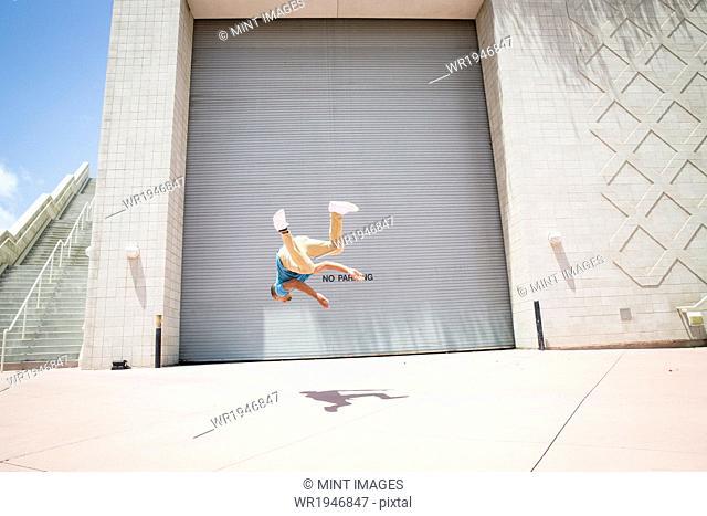 Young man somersaulting in front of a garage door