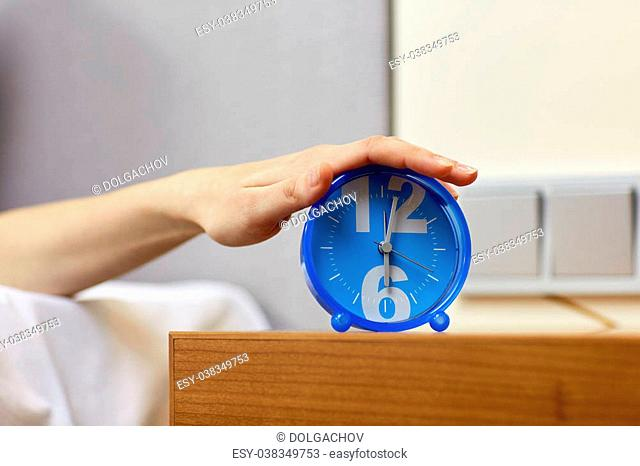 morning, awakening and people concept - close up of female hand on alarm clock in bedroom