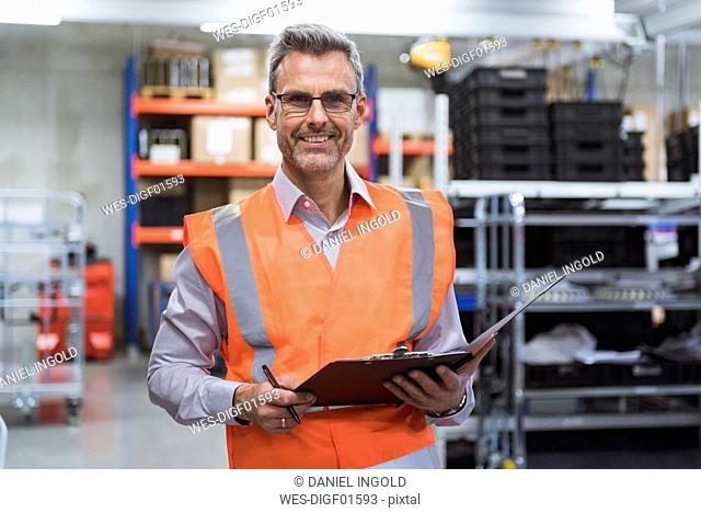 Portrait of smiling man in factory hall wearing safety vest holding clipboard