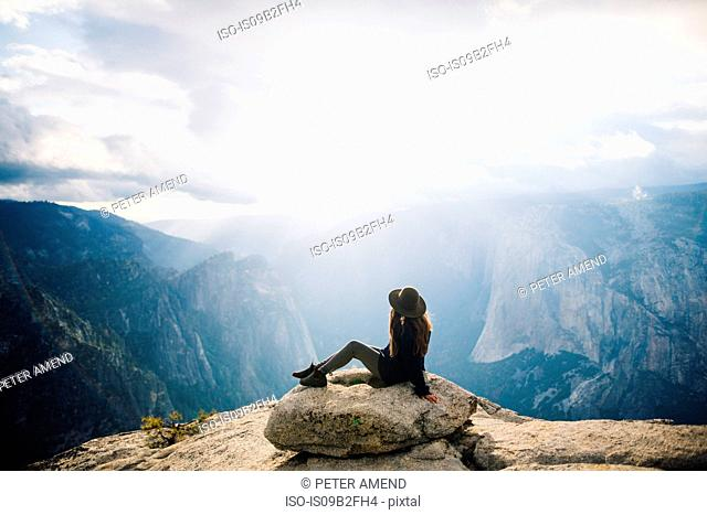 Young woman sitting at top of mountain, overlooking Yosemite National Park, California, USA