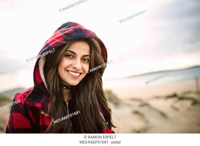 Portrait of smiling young woman wearing hooded jacket on the beach