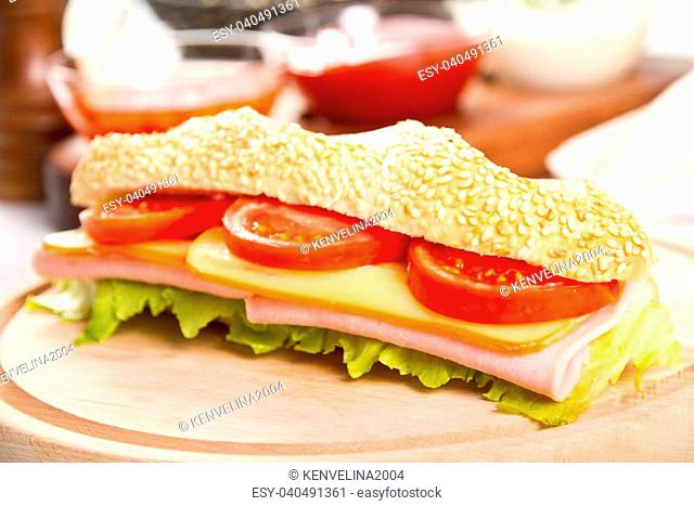 Ham and cheese sub on a wooden board