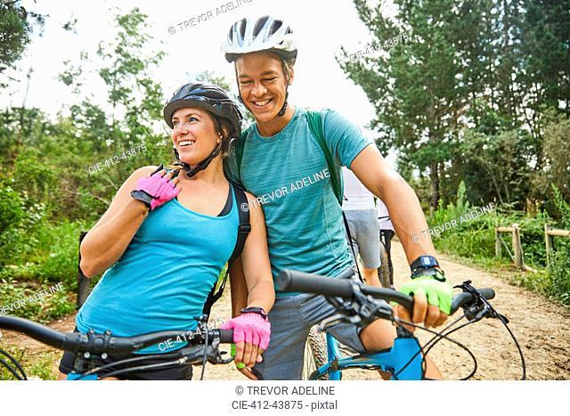 Happy, affectionate young couple mountain biking