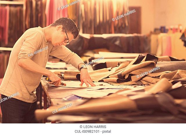Man cutting leather with utility knife in leather jacket manufacturers