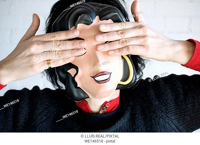 Young woman with mask, covering her eyes with the hands