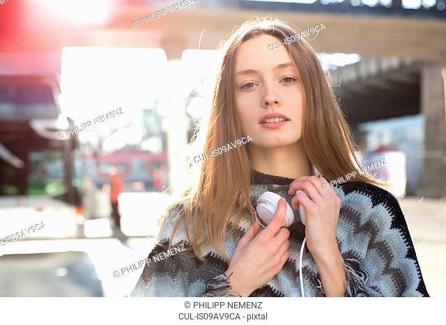 Portrait of beautiful mid adult woman wearing headphones in city