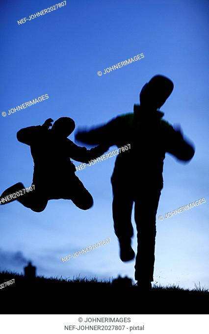 Silhouette of two people jumping
