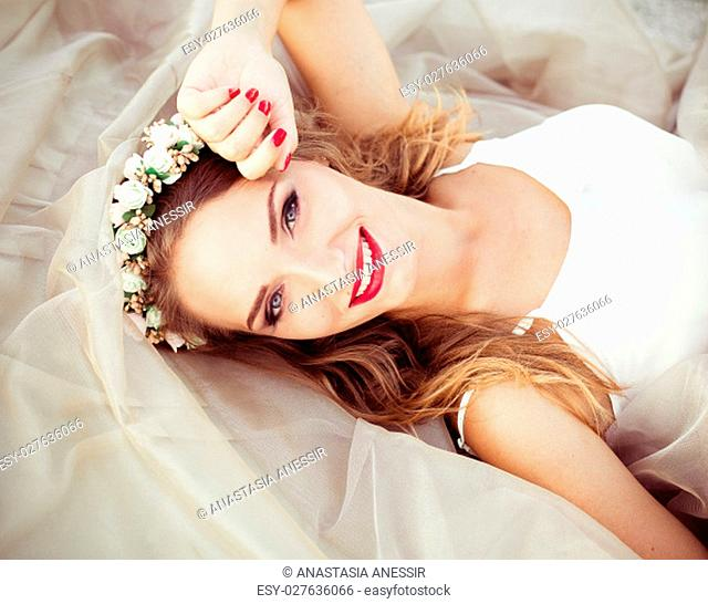Smiling cute attractive girl in white dress and wreath of white beautiful flowers. Beautiful healthy whitesmile. Top view. Top from above