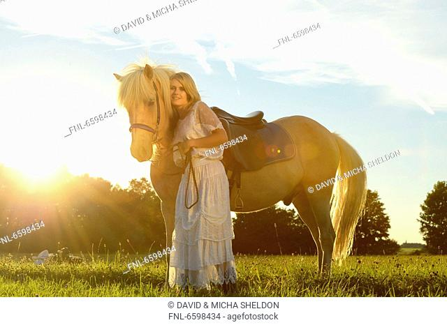 Smiling woman in white dress with horse on meadow