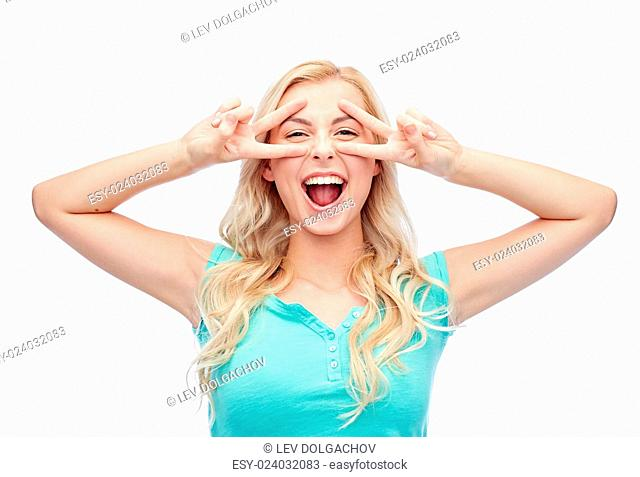 emotions, expressions, positive gesture and people concept - smiling young woman or teenage girl showing peace hand sign with both hands